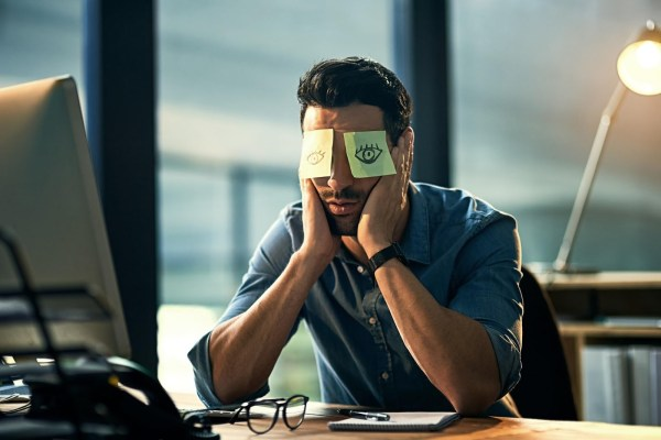 """alt=""""Business entrepreneur sited and lost in thoughts in office with computer before him"""""""